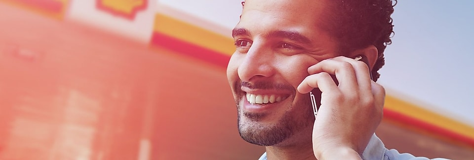 Portrait d'un businessman tunisien souriant en ligne avec son telephone mobile devant une station shell